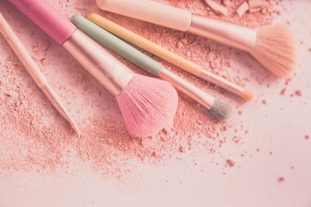 Maquillage des pinceaux avec de la poudre sur fond blanc