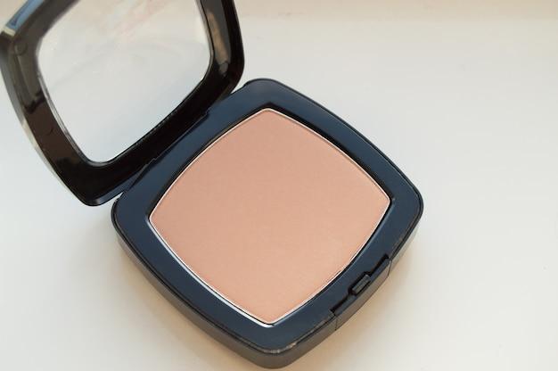 Maquillage en poudre compacte, sur fond blanc, vue de dessus
