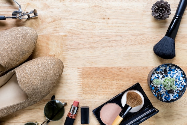 Maquillage avec des produits cosmétiques décoratifs et smartphone sur bois