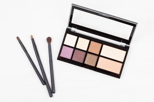 Maquillage produits cosmétiques ombres à paupières et pinceaux, mise à plat, vue de dessus.