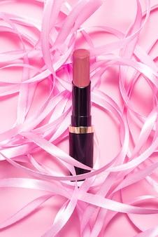 Maquillage rouge à lèvres sur une table rose décorée de ruban rose