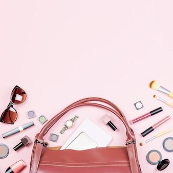 Maquillage, sac à main et lunettes de soleil sur rose