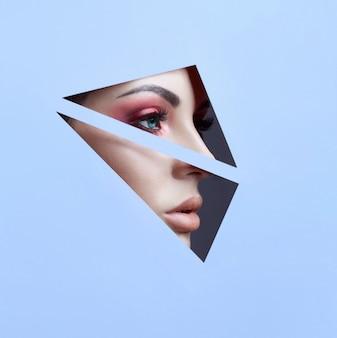 Maquillage des yeux rouges d'une jeune fille dans un trou de papier bleu
