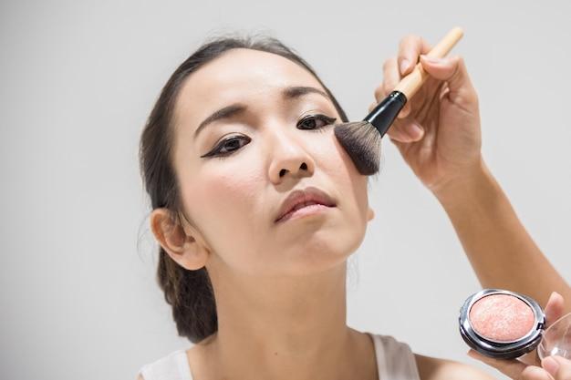 Maquilleur d'application de maquillage pour nettoyer le visage d'un modèle de mode ou d'une mariée