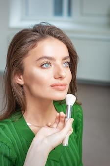 Maquilleur appliquant un maquillage professionnel de fondation tonale sur le visage de la belle jeune femme de race blanche