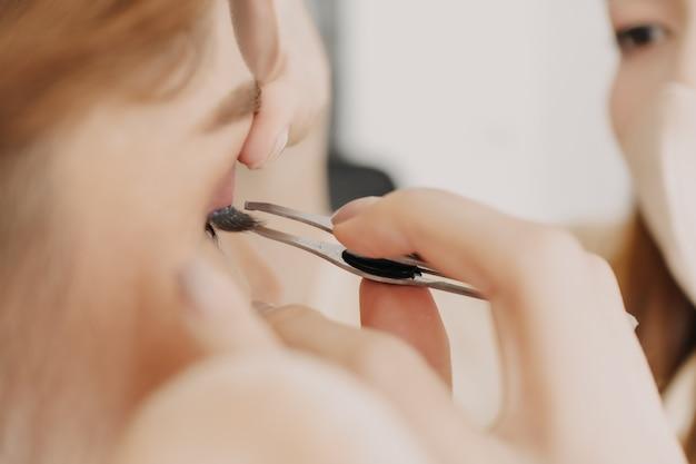 Le maquilleur applique le maquillage sur les yeux du client