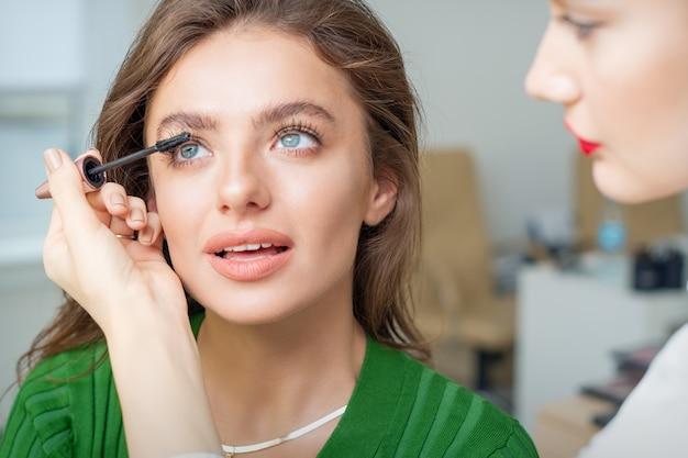 Maquilleur applique le mascara sur les cils de jeune femme de race blanche dans un salon de beauté