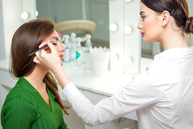 Maquilleur applique la poudre de fard à paupières sur les yeux de la jeune femme de race blanche par l'outil de brosse dans un salon de beauté
