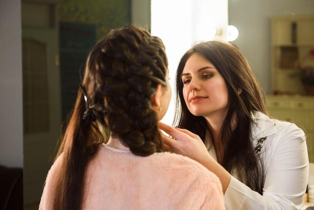 Maquilleur faisant un maquillage professionnel de jeune femme. ecole des maquilleurs.