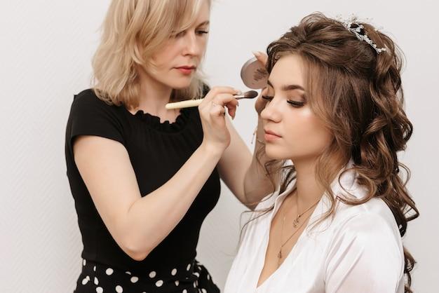 Maquilleur fait un maquillage professionnel pour une jeune mariée