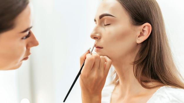 Le maquilleur maquille une cliente. peinture à lèvres