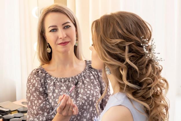 Maquilleur met le maquillage sur le modèle de la fille. appliquez de la poudre sur les pommettes et le visage.