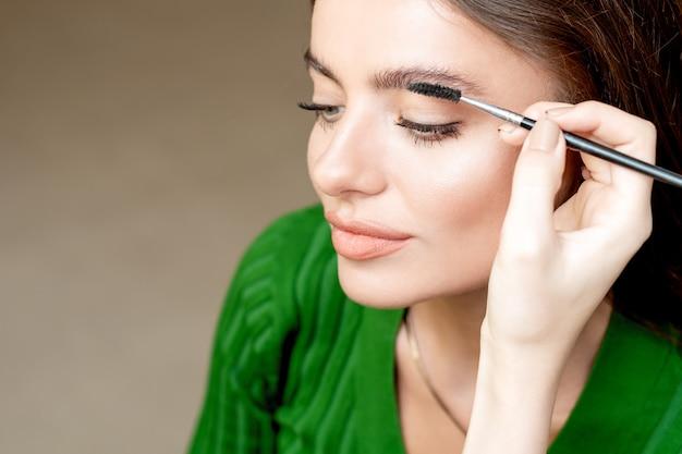 Le maquilleur peigne les sourcils avec un outil de brosse à sourcils en gros plan avec un espace de copie.