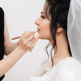 Maquilleur peint les lèvres de la femme de la mariée avec un crayon dans un salon de beauté professionnel