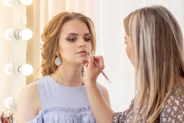 Maquilleur peint le modèle de lèvres avec un crayon à lèvres. maquillage dans les tons beiges neutres doux de jour. mariage, rencontre