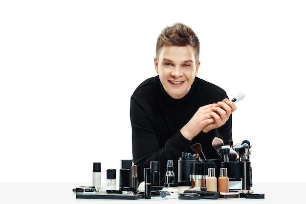 Maquilleur professionnel avec des outils isolés sur blanc. l'homme au métier féminin. concept d'égalité des sexes
