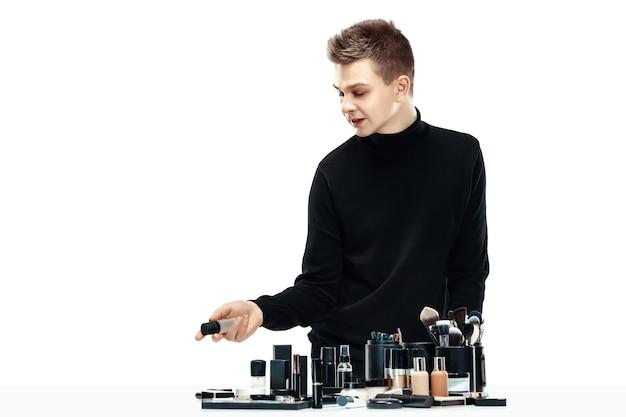 Maquilleur professionnel avec des outils isolés sur un espace blanc