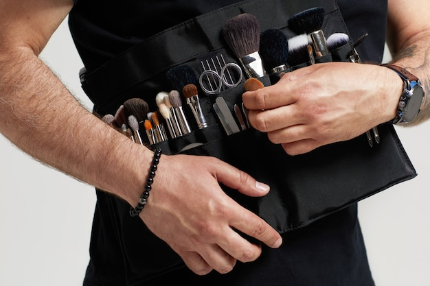 Maquilleur professionnel avec sac de ceinture avec pinceaux de maquillage