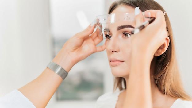 Le maquilleur vérifie les sourcils du client à l'aide d'une règle à sourcils