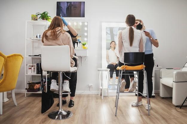 Les maquilleurs composent de jeunes femmes dans un salon de beauté. service client dans la salle intérieure pour créer une image incroyable. assistant de création de maquillage de travail. concept de style et mesure de la satisfaction. espace de copie