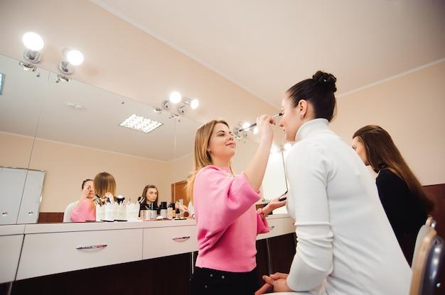 Les maquilleurs professionnels travaillent avec de belles jeunes femmes. ecole de maquillage professionnel.