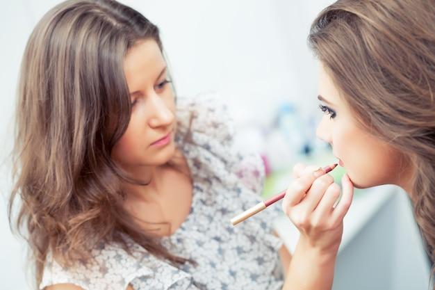 Maquilleuse appliquant un crayon à lèvres sur les lèvres des modèles