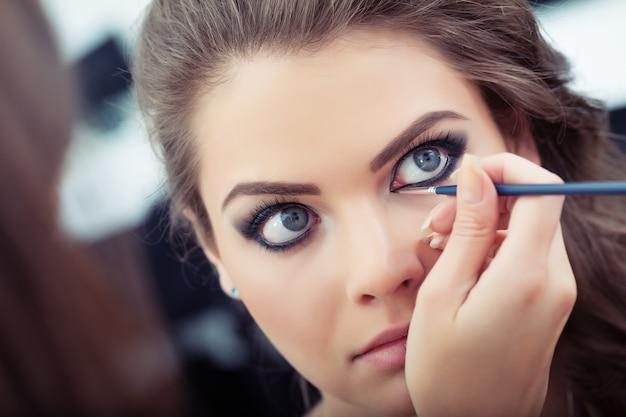 Maquilleuse appliquant un eye-liner liquide avec un pinceau en gros plan