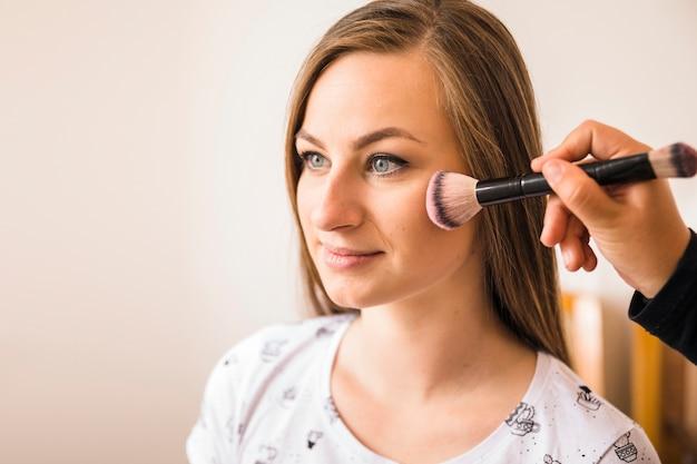 Maquilleuse appliquant le fard à joues sur le visage de la femme