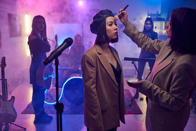 Maquilleuse appliquant le maquillage pour la jeune chanteuse avant sa performance dans le club