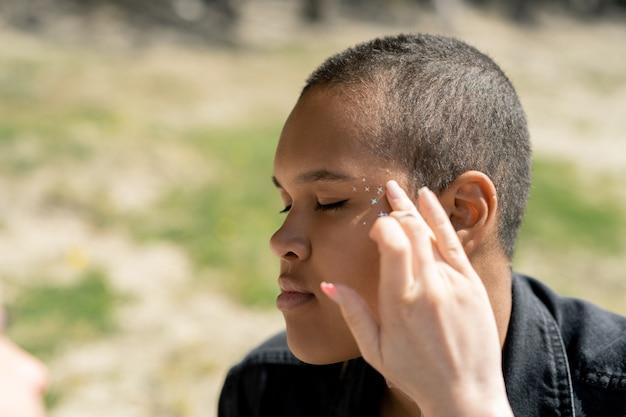 Maquilleuse appliquant des paillettes étoiles sur le temple à la femme afro-américaine aux cheveux courts à l'extérieur