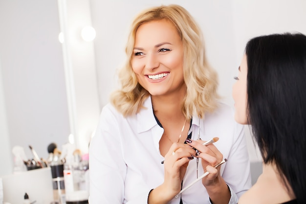 Maquilleuse appliquant la poudre pour le visage à un client dans un magasin de beauté
