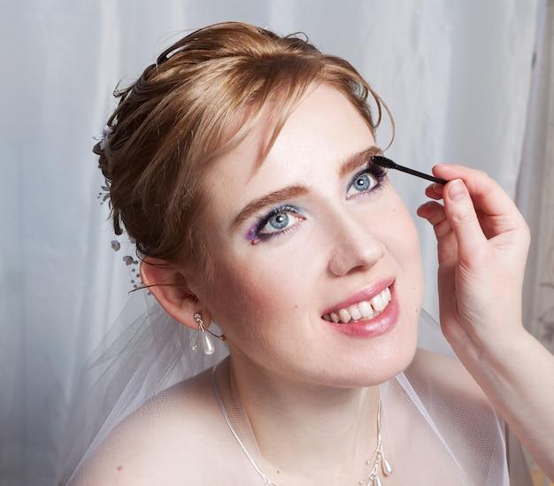 La maquilleuse applique du mascara sur les cils de la mariée. portrait en gros plan