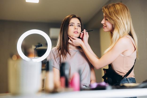 La maquilleuse applique du rouge à lèvres ou du gloss sur les lèvres de la cliente avec un pinceau. la brune et la blonde se maquillent.
