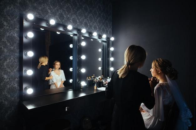 Maquilleuse applique un fard à joues sur le décolleté avec un pinceau pour modeler. maquilleuse fait un beau maquillage de mariée devant un miroir avec un portrait en studio de lampes. maquilleuse professionnelle au travail
