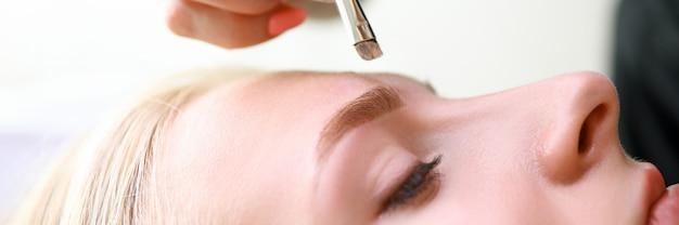 Maquilleuse applique l'ombre à paupières sur le modèle des sourcils. effet le plus naturel. la maquette est créée sur la peau. l'esthéticienne améliore la beauté naturelle. la technique implique le tatouage des sourcils avec ombrage