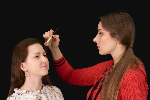 La maquilleuse applique des produits cosmétiques au modèle sur fond sombre