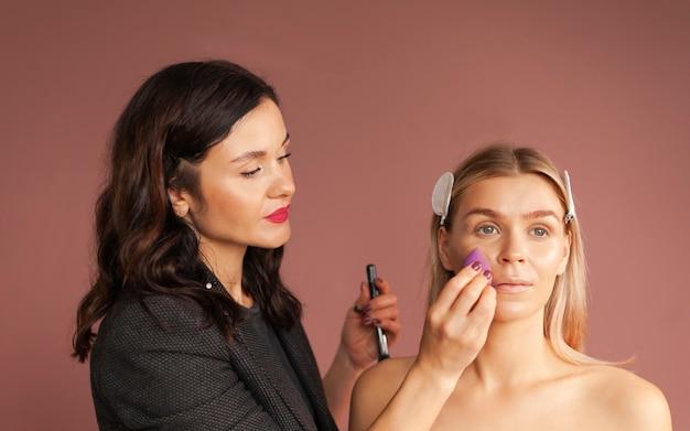 La maquilleuse applique le teint avec un œuf de maquillage éponge
