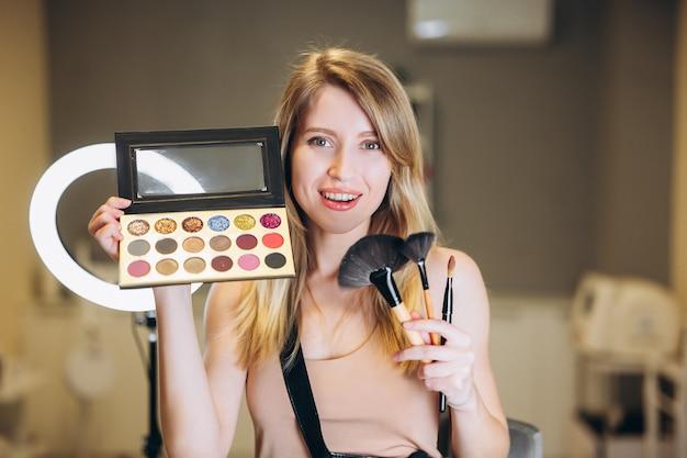 La maquilleuse blonde montre des pinceaux et une palette de fards à paupières. belle femme sourit et tient des pinceaux pour le maquillage et le fard à paupières.