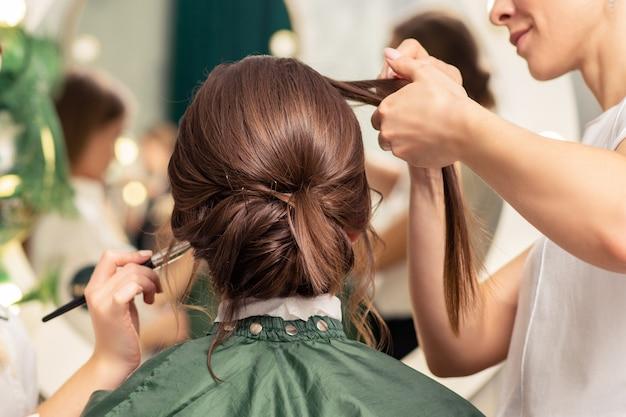 Maquilleuse et coiffeuse préparant la mariée