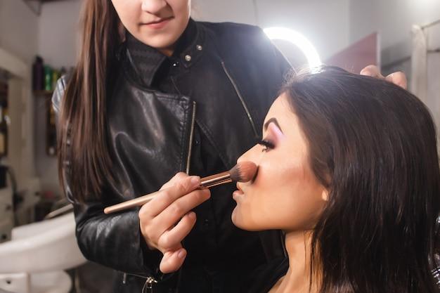 Maquilleuse colorant les joues d'une belle jeune fille dans le salon de beauté.