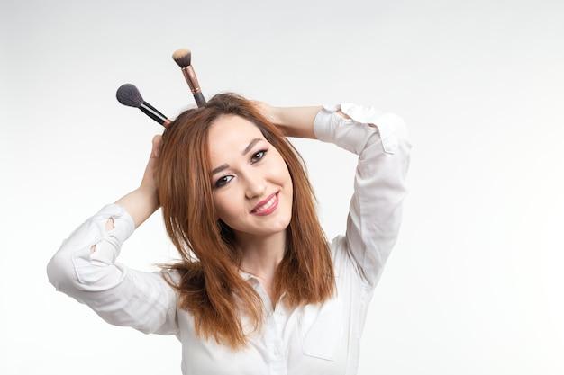 Maquilleuse, concept de beauté et de cosmétiques - maquilleuse coréenne s'amuse avec des pinceaux de maquillage