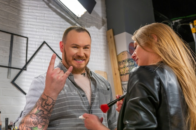 Une maquilleuse corrige un acteur de maquillage