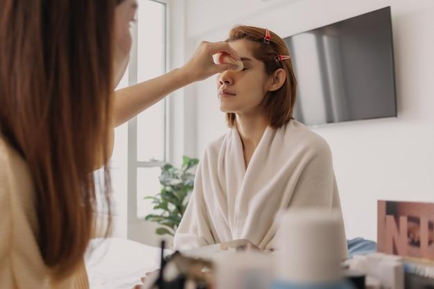 La maquilleuse est au travail et porte du maquillage sur son modèle
