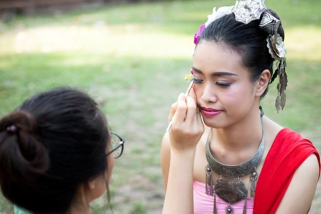 Maquilleuse fabriquant un eye liner pour une femme thaïlandaise portant des vêtements traditionnels thaïlandais