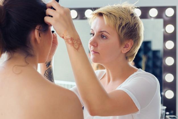 Maquilleuse faisant maquillage professionnel de jeune femme