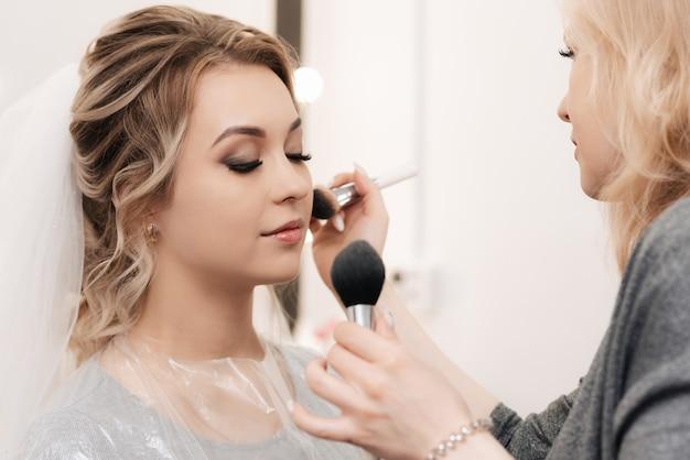 Maquilleuse fait du maquillage professionnel pour une jeune fille blonde