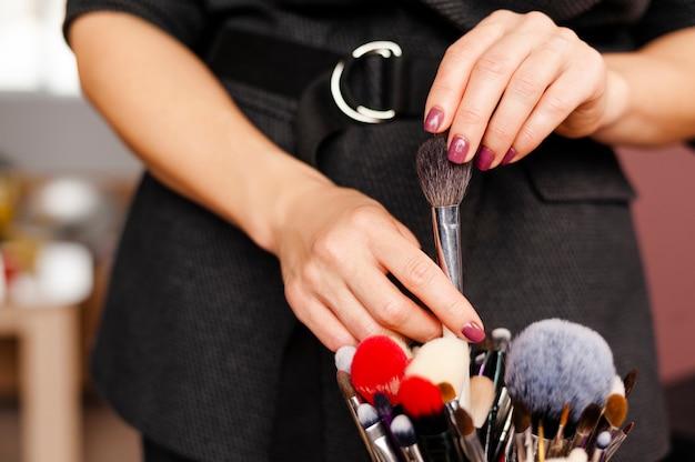 Maquilleuse femme sélectionne et sort le pinceau de l'ensemble de pinceaux de maquillage professionnel