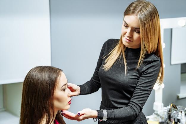 Maquilleuse jeune femme séduisante appliquant le modèle de maquillage.