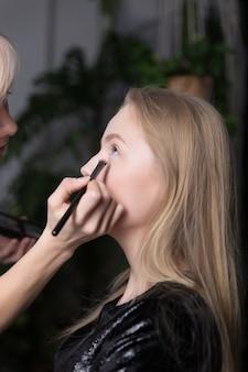 Maquilleuse maquillant une belle femme blonde à la maison