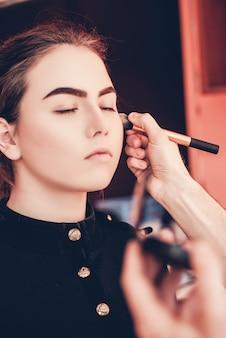 Maquilleuse maquillant une belle jeune fille en studio